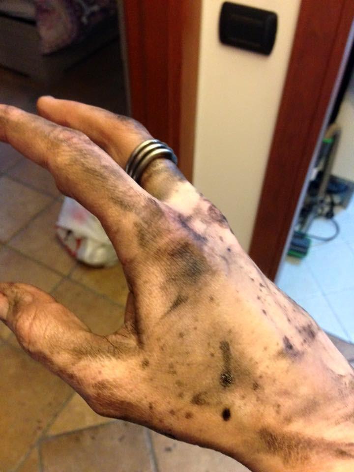 mano sporca di grasso moto